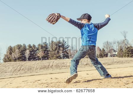 Boy pitching a baseball in the early spring