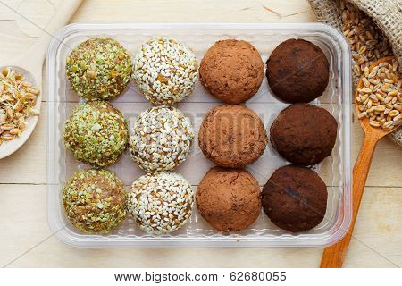 Balls From Ground Wheat Sprouts With Sesame, Pumpkin Seeds And Chocolate Sprinkles In Plastic Box; S