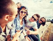 summer holidays and teenage concept - group of teenagers hanging out outside poster