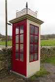 Earliest model of standard UK telephone kiosk the K1. This is a replica after the original was accidentally destroyed during the filming of the 1986 film Comrades. Tyneham Dorset England United Kingdom. poster