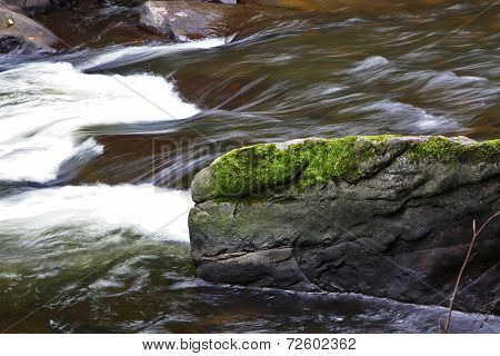 Large Moss Covered Rock In River Rapids