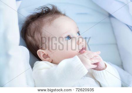 Beautiful Little Baby Relaxing In A Stroller Wearing A Warm Hite Sweater