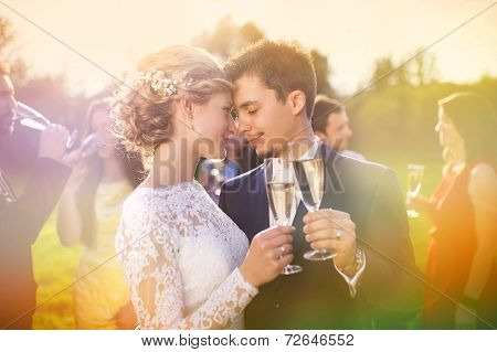 Newlyweds clinking glasses outside