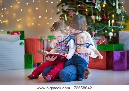 Cute Happy Boy Reading To His Toddler Sister And Newborn Baby Brother Under Beautiful Christmas Tree