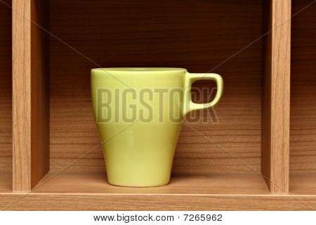 Light green coffee cup on wooden shelf
