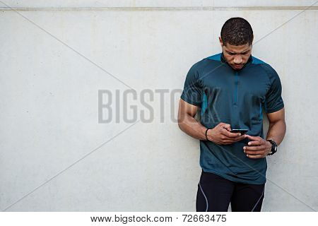 Attractive sting build runner resting after self training standing on white wall background, male runner using mobile phone, dark skinned jogger holding mobile smartphone standing outdoors poster