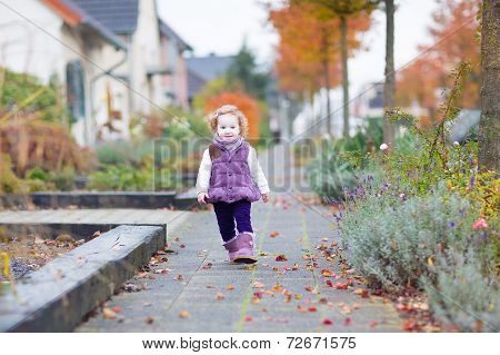 Adorable Toddler Girl Walking Down A Beautiful Road In A Little German Village In Autumn
