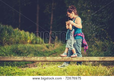 Mother helping her child balancing on a tree