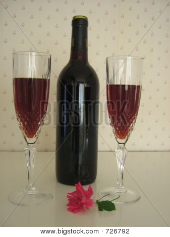Celebrating.Two Cups Of Red Wine,Bottle Of Wine,And Red Rose