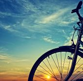 Beautiful close up scene of bicycle at sunset sun on blue sky with vintage colors silhouette of bike forward to sun wonderful rural of Mekong Delta Vietnam countryside poster