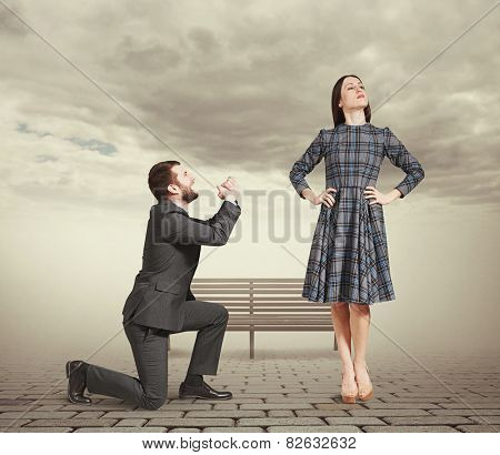 sad man kneeling on one knee, looking at young attractive woman and asking for forgiveness. photo at outdoor