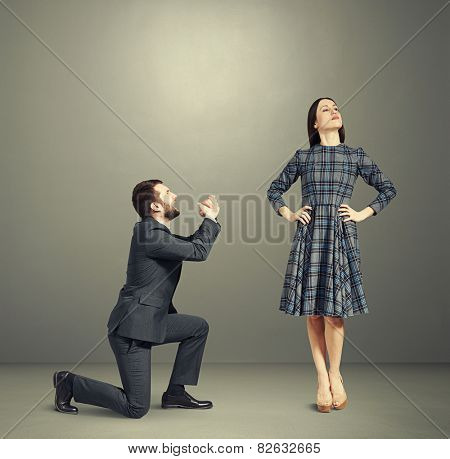 crying man looking at young beautiful woman and asking for forgiveness. photo over dark background