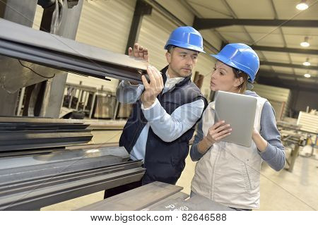 Supplier with engineer checking on production in factory