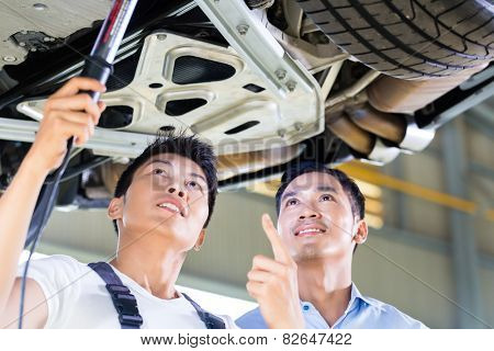 Asian Chinese car mechanic with customer looking at auto floor with lamp poster