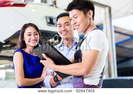 Car mechanic and Asian customer couple going through checklist with auto on hoist in the background of workshop