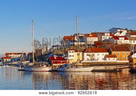 Boats moored with lowered sails on the fjord. Boats moored next winter secured. In the background the Norwegian port characteristic buildings. Rocky island with buildings. Boats on the water. Winter scenery. Kragero Telemark municipality. Region of southe poster