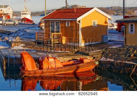 Small Orange Motorboat Reflecting In The Water