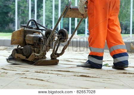 Worker in overalls controls plate compactor