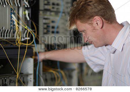 Telecom Engineer Looks On Multiplexer