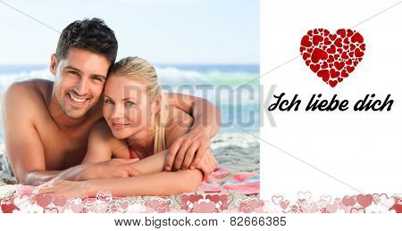Lovers lying down on the beach against ich liebe dich