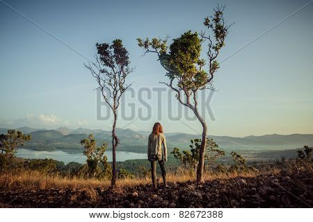 Woman Standing Between Two Trees