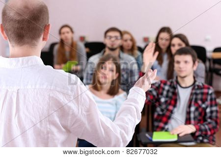 Group of students sitting in classroom and  listening teacher