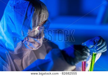 science, chemistry, biology, medicine and people concept - close up of young female scientist holding tubes with chemicals making test or research in laboratory