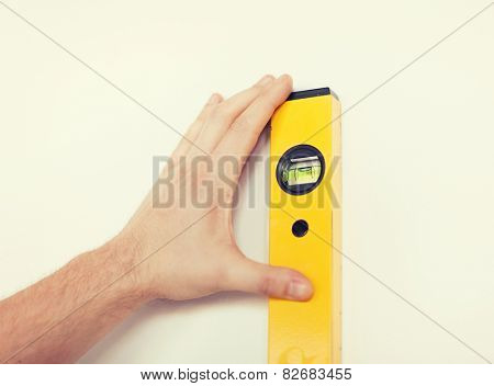 repair, building, technology and home concept - close up of male with spirit level mesuring wall