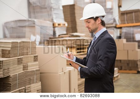 Serious warehouse manager checking inventory in warehouse