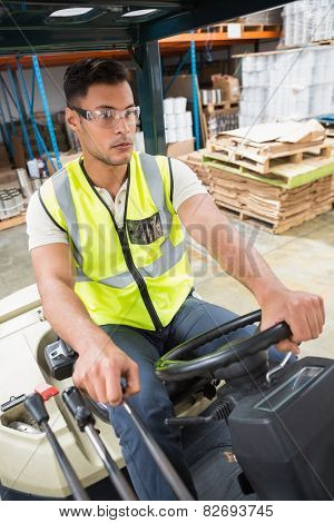 Portrait of driver operating forklift machine in warehouse