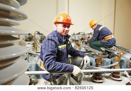 Electricians lineman repairman worker at huge power industrial transformer installation work