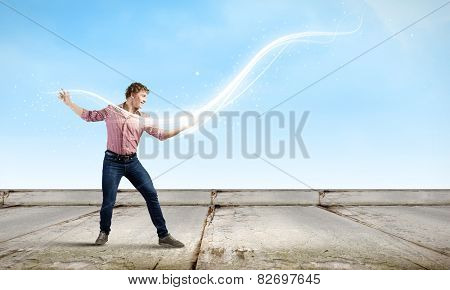 Young man in casual throwing magic light