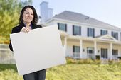 Smiling Hispanic Female Holding Blank Sign In Front of Beautiful House. poster