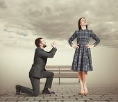 sad man kneeling on one knee, looking at young attractive woman and asking for forgiveness. photo at outdoor poster