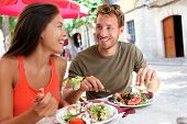 Restaurant tourists couple eating at outdoor cafe. Summer travel people eating healthy food together at lunch during holidays in Mallorca, Spain. Asian Caucasian multiracial young adults. poster