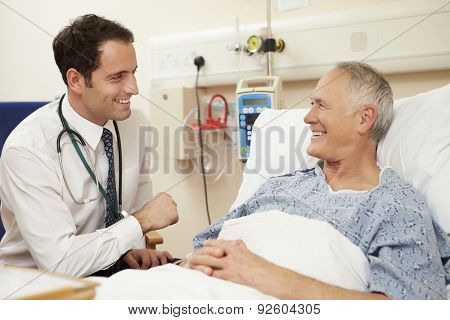 Doctor Sitting By Male Patient's Bed In Hospital