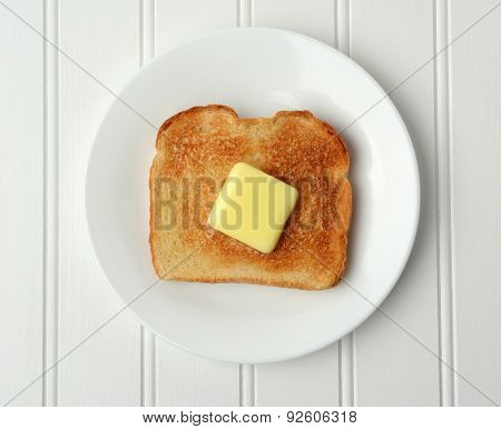 Overhead shot of a piece of buttered toast. A pat of melting butter is in the middle of the toasted white bread on a white plate