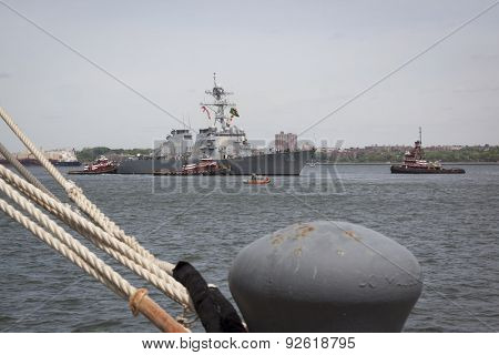 STATEN ISLAND, NY - MAY 20 2015: USS Barry (DDG 52) is guided into port by McAllister tugboats at Sullivans Pier, with a mooring bollard in the foreground at the beginning of Fleet Week.