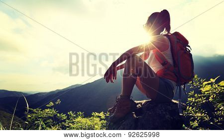 woman backpacker enjoy the view at mountain peak cliff