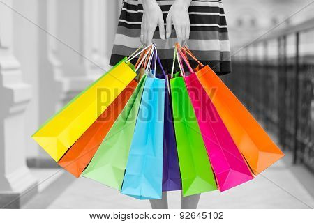 Woman Holding Colourful Shopping Bags At The Mall. Black And White Background.