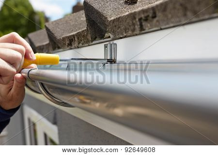 Close Up Of Man Replacing Guttering On Exterior Of House poster