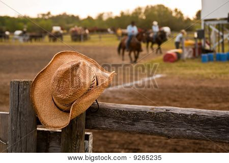 A Straw Cowboy Hat Hung On The Fence At A Rodeo With Horses And Riders In The Background