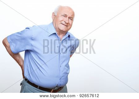 Exhausted grandfather touching his back