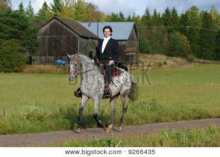 A man in tuxedo riding appaloosa mare with western tack poster