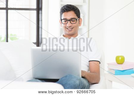 Good looking Indian guy with laptop computer working from home. Asian man using internet indoor, relaxed and sitting on sofa. Handsome male model.