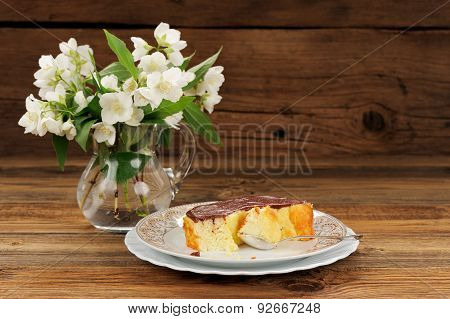 Homemade Baked Pudding With Chololate Icing And Jasmine Flowers On Wooden Background