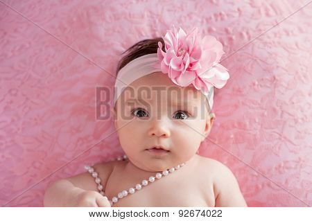 Baby Girl With A Large, Pink, Flower Headband And Pearls