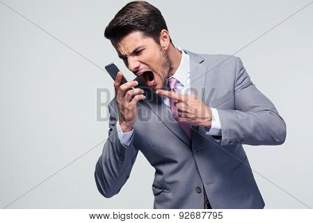 Angry businessman shouting on the phone over gray background
