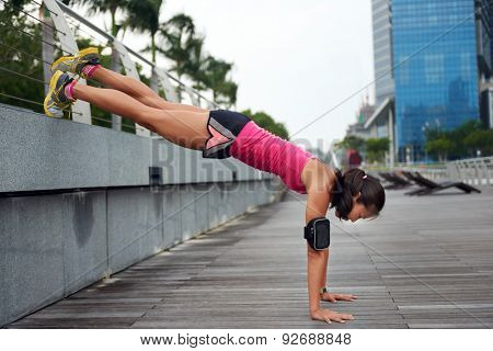 active strong woman doing pushup strengthening workout along outdoor city sidewalk with elevated legs