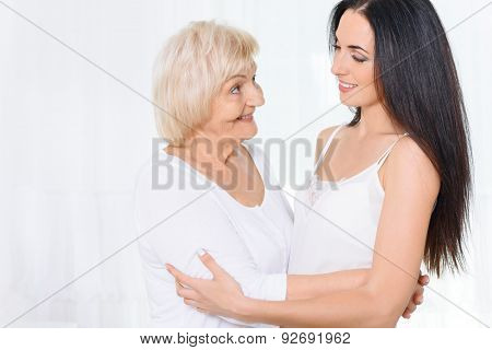 Granny standing and hugging granddaughter